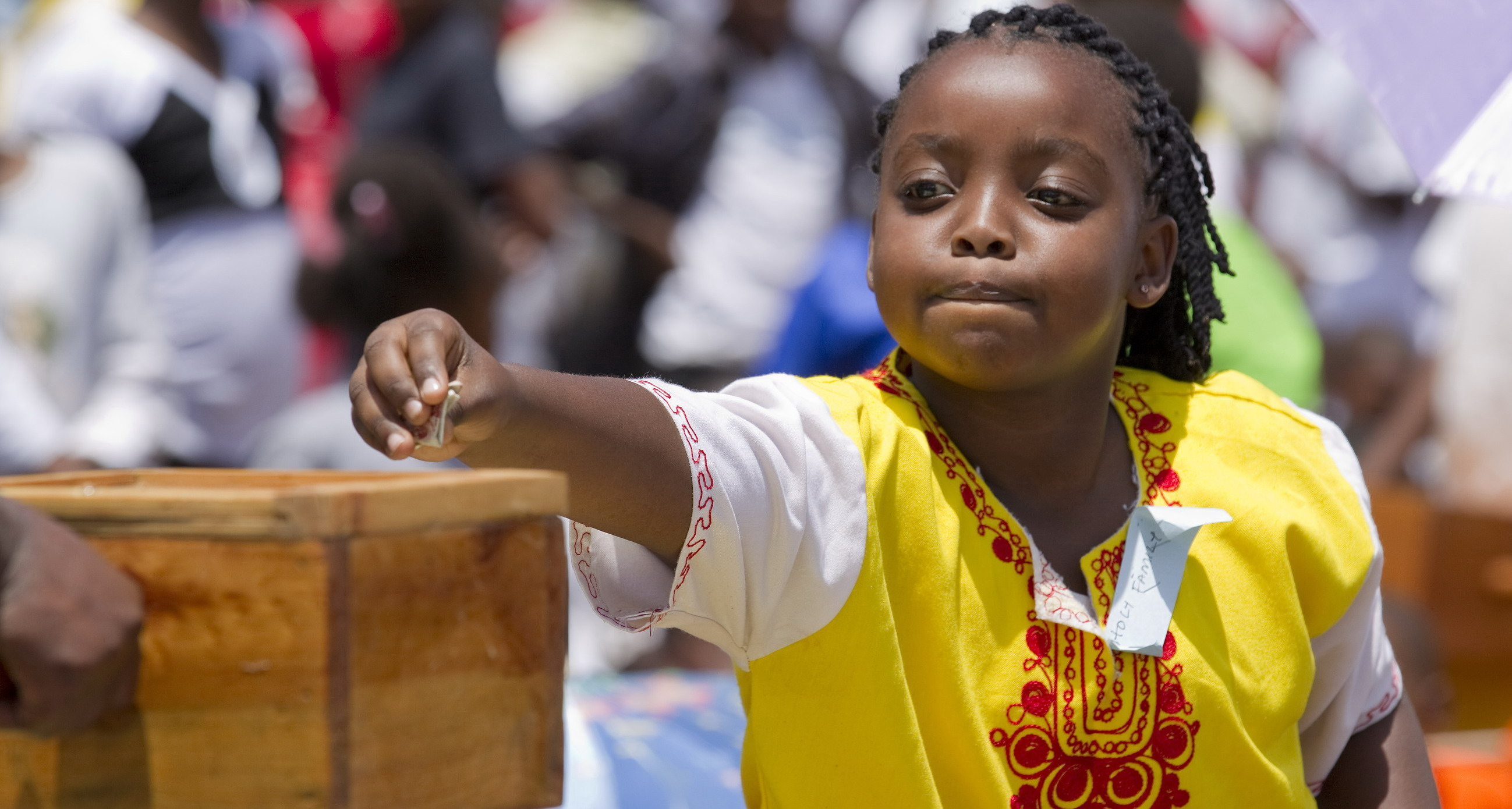 A girl makes an offering during Mass marking Missionary Childhood Day in Nairobi, Kenya, Feb. 19. Held annually by the Pontifical Missionary Childhood society, the outdoor service drew more than 30,000 children from around the Archdiocese of Nairobi. (CNS photo/Nancy Wiechec) See KENYA-CHILDREN and KENYA-PMC