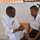 P. Charles Gachara confessa bambina della Prima Comunione