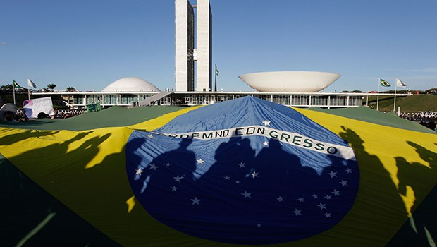 Demonstrators open a Brazil's flag in front of the National Congress during a protest in Brasilia, Brazil, Wednesday, June 26, 2013. The wave of protests that hit Brazil on June 17 began as opposition to transportation fare hikes, then expanded to a list of causes including anger at high taxes, poor services and high World Cup spending, before coalescing around the issue of rampant government corruption. (AP Photo/Eraldo Peres)