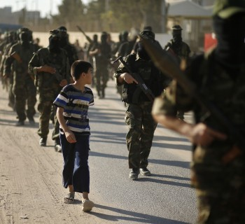 A Palestinian boy looks at Hamas militants as they take part in a protest against peace talks between Israel and the Palestinians, in central Gaza Strip September 20, 2013.   REUTERS/Mohammed Salem (GAZA - Tags: POLITICS CIVIL UNREST)