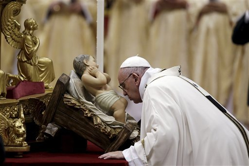 Pope Francis kisses a statue of Baby Jesus as he celebrates the Christmas Eve Mass in St. Peter's Basilica at the Vatican, Thursday, Dec. 24, 2015. (AP Photo/Gregorio Borgia)