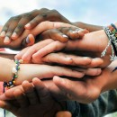 Adolescentes multirrraciais juntando as mãos em cooperação. (Foto: Shutterstock)