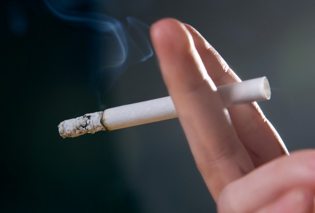 Woman's fingers with smoking cigarette macro shot