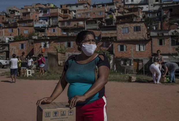 Moradora recebe uma cesta de alimentos e produtos de higiene doados na favela do Vale das Virtudes, São Paulo, 12 de junho de 2020. (Victor Moriyama/Bloomberg)