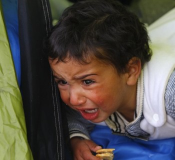 A migrant baby, waiting to cross the Greek-Macedonian border with family members, cries at a tent near the village of Idomeni, Greece March 8, 2016. REUTERS/Ognen Teofilovski